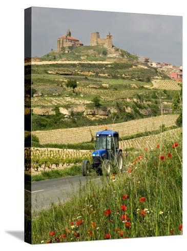 Blue tractor on rural road, San Vicente de la Sonsierra Village, La Rioja, Spain-Janis Miglavs-Stretched Canvas Print