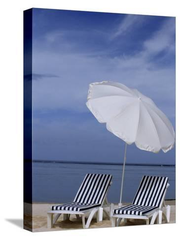 Relaxing Beach Chairs and Umbrella Await Customers-Paul Sutherland-Stretched Canvas Print