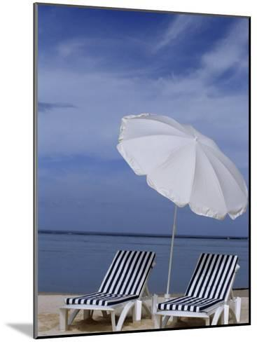 Relaxing Beach Chairs and Umbrella Await Customers-Paul Sutherland-Mounted Photographic Print