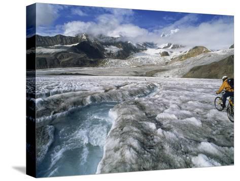 Mountain Biking over Black Rapids Glacier-Bill Hatcher-Stretched Canvas Print