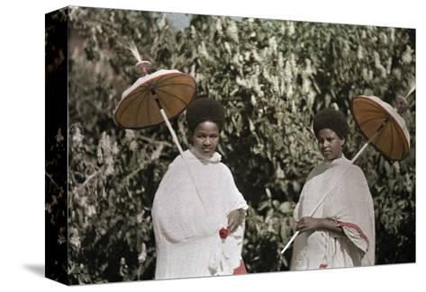 Two Amharic Women Pose Holding Umbrellas to Shade Themselves-W^ Robert Moore-Stretched Canvas Print