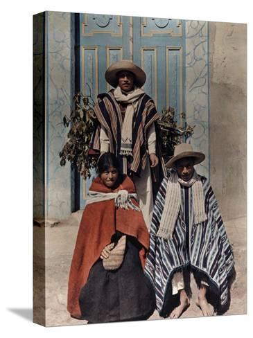 Three Poncho-Clad Quichua Indians Stand in Front of a Colorful Door-Jacob Gayer-Stretched Canvas Print