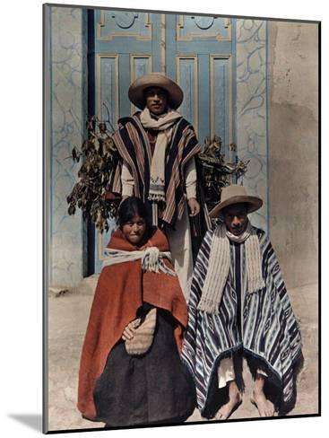 Three Poncho-Clad Quichua Indians Stand in Front of a Colorful Door-Jacob Gayer-Mounted Photographic Print