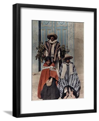Three Poncho-Clad Quichua Indians Stand in Front of a Colorful Door-Jacob Gayer-Framed Art Print