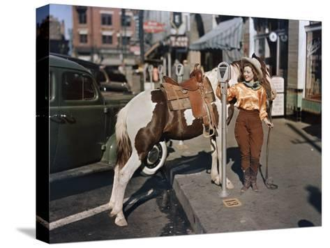Cowgirl Puts a Nickel in an El Paso Parking Meter to Hitch Her Pony-Luis Marden-Stretched Canvas Print