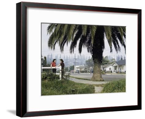 Two Girls Chat on a Street with Oil Derricks in the Background-B^ Anthony Stewart-Framed Art Print