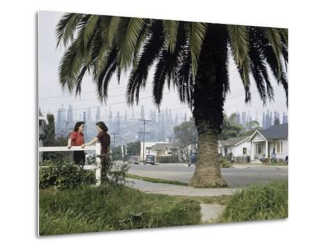 Two Girls Chat on a Street with Oil Derricks in the Background-B^ Anthony Stewart-Metal Print