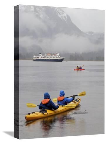 Kayaking in Khutze Inlet Near a Cruise Ship-Michael Melford-Stretched Canvas Print