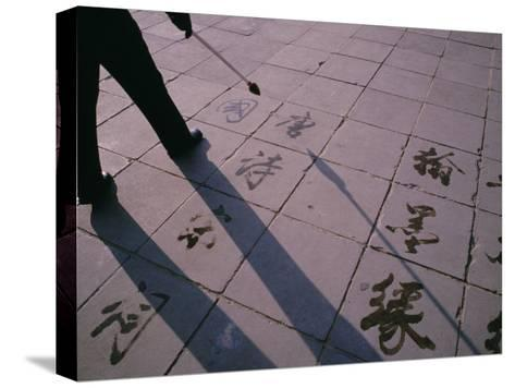 Man Paints Chinese Calligraphy in Water with a Long Modified Brush-xPacifica-Stretched Canvas Print