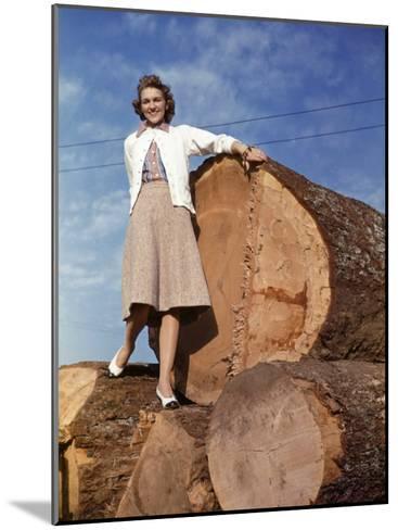 Woman Stands on a Pile of Gigantic Douglas Fir Logs-Maynard Owen Williams-Mounted Photographic Print