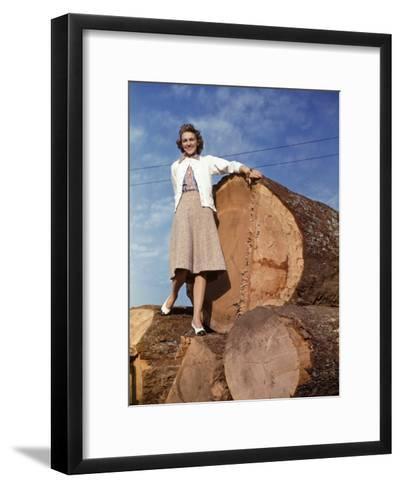 Woman Stands on a Pile of Gigantic Douglas Fir Logs-Maynard Owen Williams-Framed Art Print