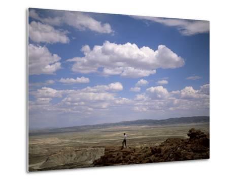 Environmental Activist Observes the Rock Formations of Adobe Town-Joel Sartore-Metal Print