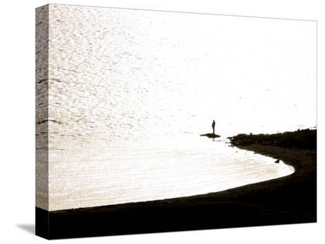 Silhouetted Person on a Point of Land Jutting Out into Calm Water-Mattias Klum-Stretched Canvas Print