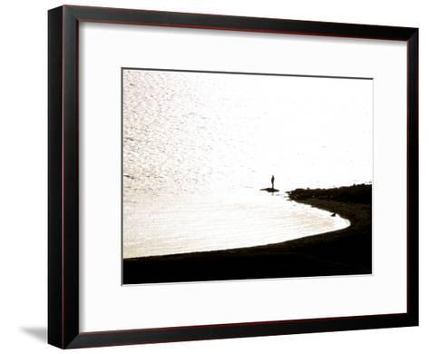 Silhouetted Person on a Point of Land Jutting Out into Calm Water-Mattias Klum-Framed Art Print