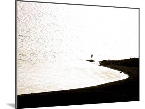 Silhouetted Person on a Point of Land Jutting Out into Calm Water-Mattias Klum-Mounted Photographic Print