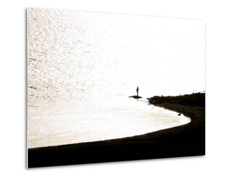 Silhouetted Person on a Point of Land Jutting Out into Calm Water-Mattias Klum-Metal Print