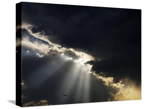 Crepuscular Rays Illuminate an Airplane Flying Below Heavy Clouds-Mattias Klum-Stretched Canvas Print