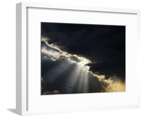 Crepuscular Rays Illuminate an Airplane Flying Below Heavy Clouds-Mattias Klum-Framed Art Print
