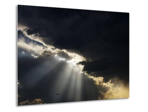 Crepuscular Rays Illuminate an Airplane Flying Below Heavy Clouds-Mattias Klum-Metal Print