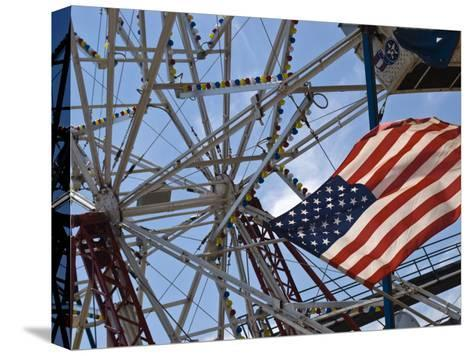Flag in Front of a Ferris Wheel Against a Summer Sky-Todd Gipstein-Stretched Canvas Print