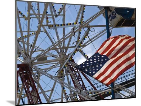 Flag in Front of a Ferris Wheel Against a Summer Sky-Todd Gipstein-Mounted Photographic Print