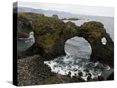 Sea Pounds Volcanic Rock Along the Coast of Iceland-Annie Griffiths Belt-Stretched Canvas Print