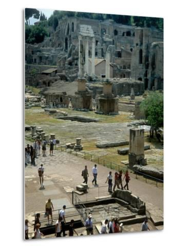 Tourists Walk Through Rome's Ancient Forum with Palatine Hill Behind-O^ Louis Mazzatenta-Metal Print