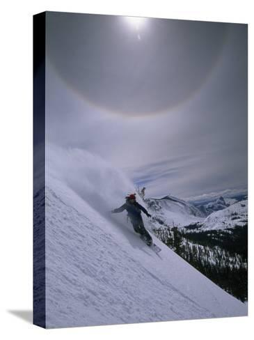 Snowboarding Down a Peak in Yosemite High Country-Bill Hatcher-Stretched Canvas Print