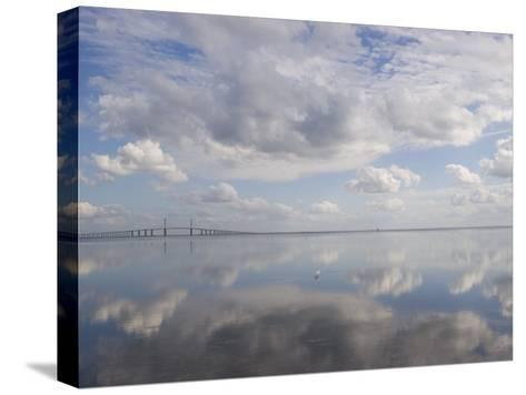 Clouds and Sky are Reflected in Calm Water with Bridge-Skip Brown-Stretched Canvas Print