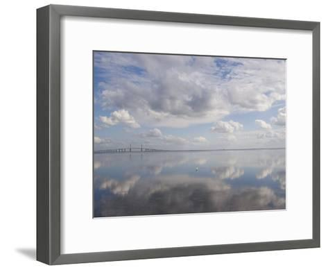 Clouds and Sky are Reflected in Calm Water with Bridge-Skip Brown-Framed Art Print