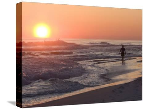 Silhouetted Man Walking Along the Beach at Sunset-Marc Moritsch-Stretched Canvas Print