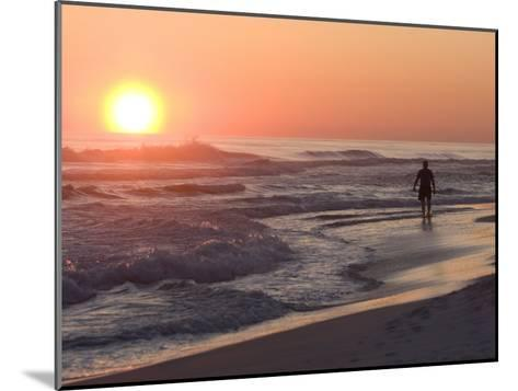 Silhouetted Man Walking Along the Beach at Sunset-Marc Moritsch-Mounted Photographic Print