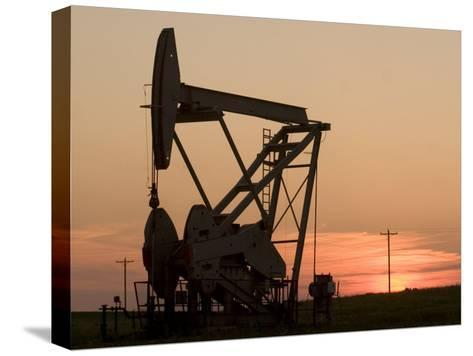 Oil Drilling Pump Silhouetted Against the Sunset in North Dakota-Phil Schermeister-Stretched Canvas Print