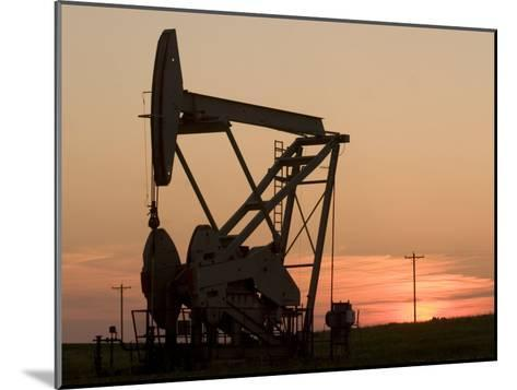 Oil Drilling Pump Silhouetted Against the Sunset in North Dakota-Phil Schermeister-Mounted Photographic Print