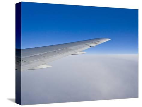 Airplane Just Above Clouds with Sky Split in Blue and White Layers-Mike Theiss-Stretched Canvas Print