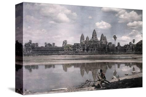 Person Sits by a Moat Which Surrounds the Towers of Angkor Vat-Gervais Courtellemont-Stretched Canvas Print