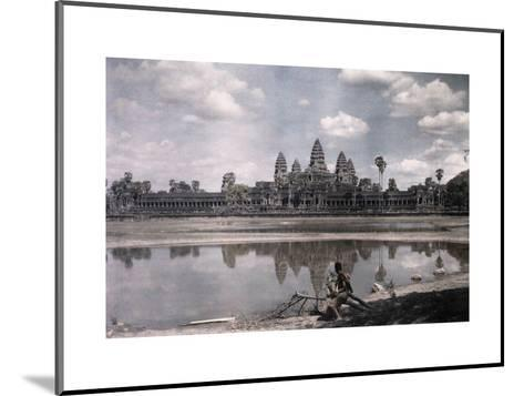 Person Sits by a Moat Which Surrounds the Towers of Angkor Vat-Gervais Courtellemont-Mounted Photographic Print