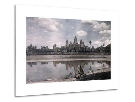 Person Sits by a Moat Which Surrounds the Towers of Angkor Vat-Gervais Courtellemont-Metal Print