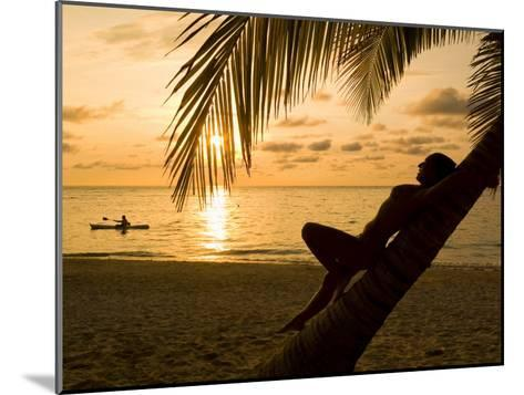 Woman Resting on a Palm Tree at Sunset, Sunset over the Caribbean Sea-Richard Nowitz-Mounted Photographic Print
