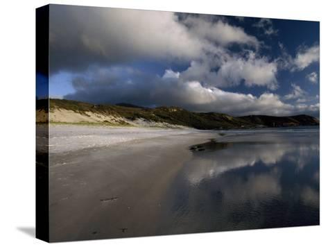 Sunlight Pierces Storm Clouds Illuminating an Empty and Remote Beach-Jason Edwards-Stretched Canvas Print