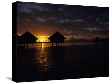 Bungalows over the Water at Sunset at an Exclusive Hotel on Tahiti-Paul Sutherland-Stretched Canvas Print