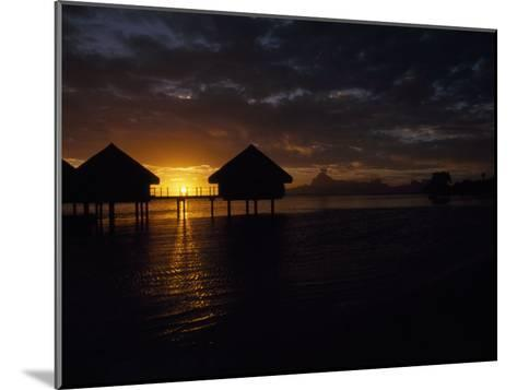 Bungalows over the Water at Sunset at an Exclusive Hotel on Tahiti-Paul Sutherland-Mounted Photographic Print