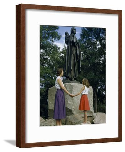 Mother and Daughter Holding Hands Stand Beside Statue of Sacagawea-Ralph Gray-Framed Art Print