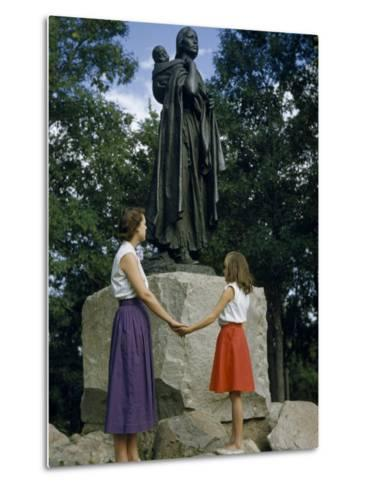 Mother and Daughter Holding Hands Stand Beside Statue of Sacagawea-Ralph Gray-Metal Print