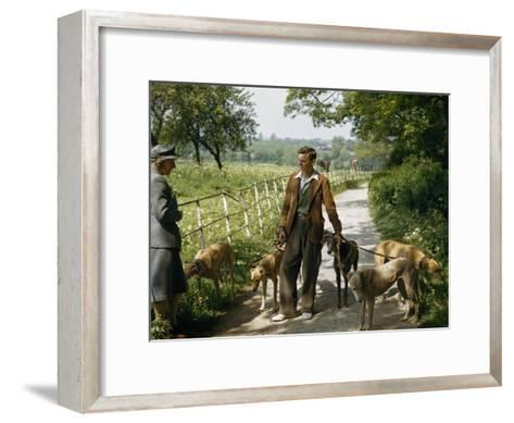 Woman Talks with a Man Walking Racing Greyhounds-B^ Anthony Stewart-Framed Art Print