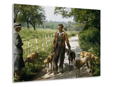 Woman Talks with a Man Walking Racing Greyhounds-B^ Anthony Stewart-Metal Print