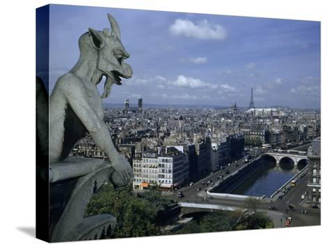 Gargoyle on Notre Dame Looks Down on a Densely Packed Cityscape-Justin Locke-Stretched Canvas Print