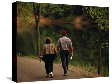 Couple Walking by the Water Along a Park Road-Raymond Gehman-Stretched Canvas Print