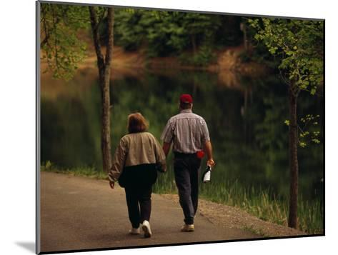 Couple Walking by the Water Along a Park Road-Raymond Gehman-Mounted Photographic Print