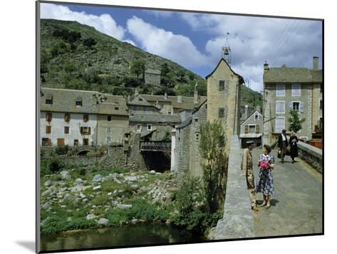 People in Riverside Village Walk across an Old Bridge-Walter Meayers Edwards-Mounted Photographic Print